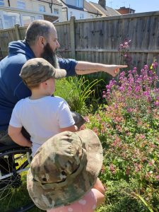 Wheelchair user in garden with grandchildren