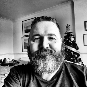 Man, over 50, short beard, forcing a smile