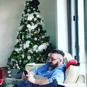 Bearded man sat looking at phone on Christmas Day